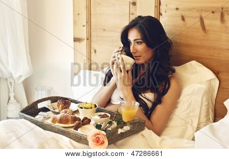 beautiful woman having breakfast in the hotel bed