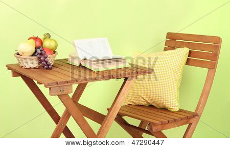 Wooden table with fruit and book on it on green background