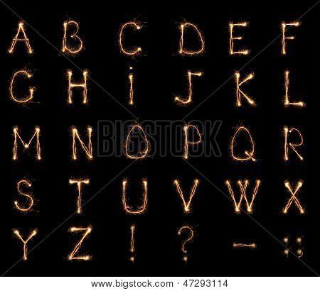 Alphabet sparklers on black background