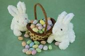 stock photo of scat  - Miniature two tone wicker basket with tall handle at slant degree angle filled with colorful speckled egg jelly beans with more eggs scatted in front of basket - JPG