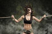 stock photo of black tie  - amazing brunette woman with flying hair and fitness body wearing sexy black top and shorts - JPG