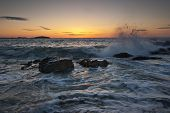 picture of marblehead  - Waves crash and shoot into the air on a rocky beach at sunrise - JPG