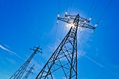 stock photo of electric station  - a power mast of a high voltage transmission line against blue sky with sun - JPG