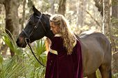 stock photo of bareback  - medieval woman in dress with horse in forest - JPG