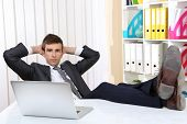 foto of table manners  - Businessman resting at his office with his shoes on table - JPG