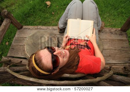 Woman Smiles While Reading A Book On A Unique Bench