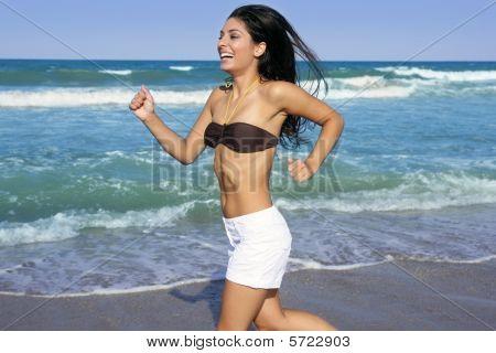 Hermosa morena de verano niña saltando en la playa