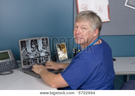 Doctor Reviewing Mri On Laptop