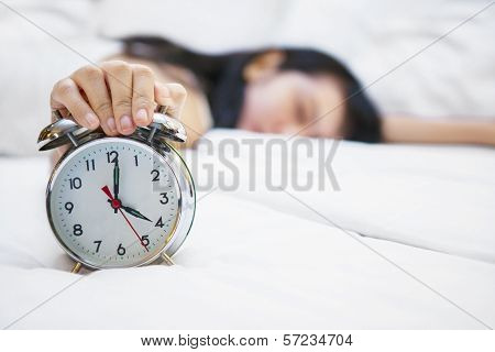 Alarm Clock With Sleeping Female On Bed