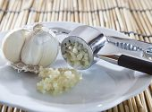 pic of crusher  - fresh garlic crushed by garlic crusher on white dish on kitchen table top use for food spice and ingredient healthy topic - JPG