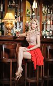 image of provocative  - Attractive blonde woman with long hair in elegant nude and red dress sitting on bar stool. Gorgeous blonde model showing her long legs with high heels posing provocatively in vintage bar