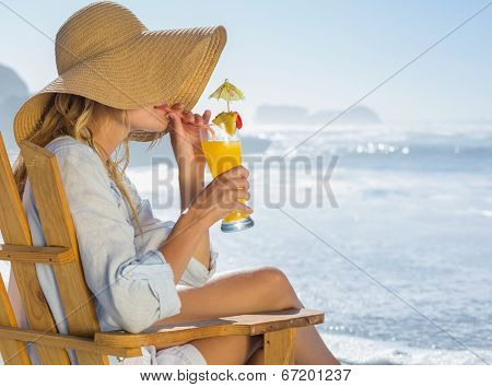 Smiling blonde relaxing in deck chair by the sea sipping cocktail on a sunny day