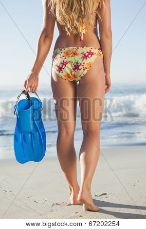 Woman holding flippers walking towards the sea on a sunny day