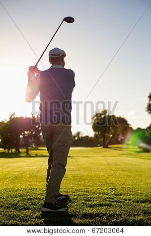 Golfer teeing off for the day on a sunny morning at the golf course