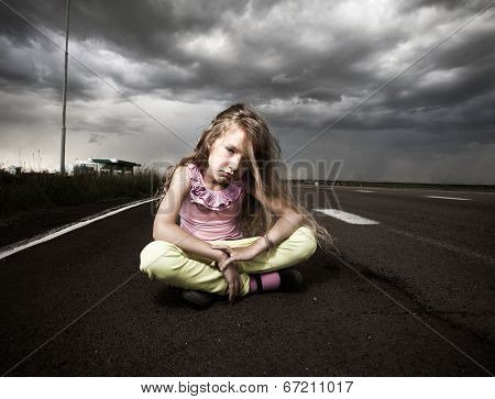 Sad girl near road. Child outdoors