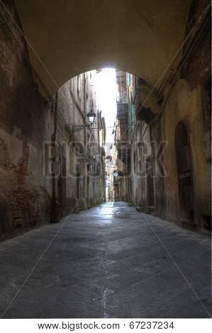 Narrow Alley With Old Buildings In Medieval Town of Pisa, Tuscany, Italy