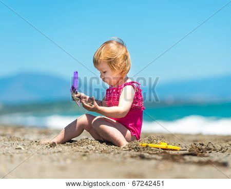 baby girl playing in the sand with a shovel on the beach