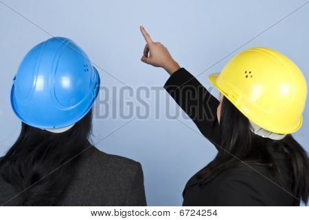 Back Of Two Architects Women Pointing Up