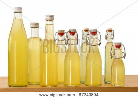 Different small bottles filled with elderflower syrup