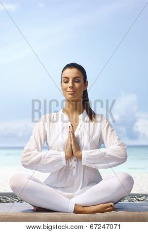 Young woman meditating eyes closed in prayer position on the coast.