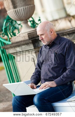 Man Sitting On A Bench Using A Laptop