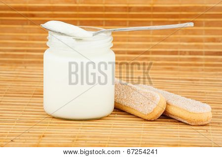 jar with home yogurt and spoon by a cookie on a straw mat