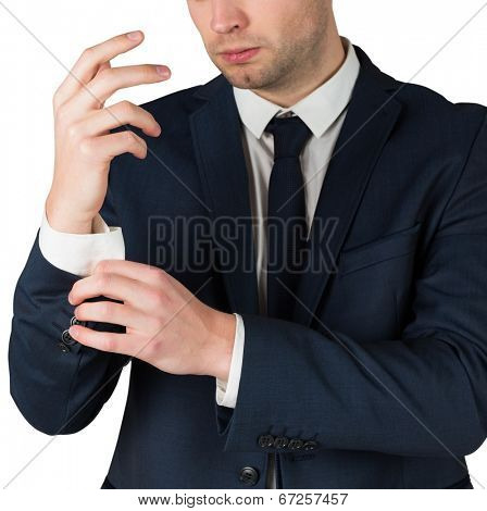 Handsome businessman adjusting his cuffs on white background