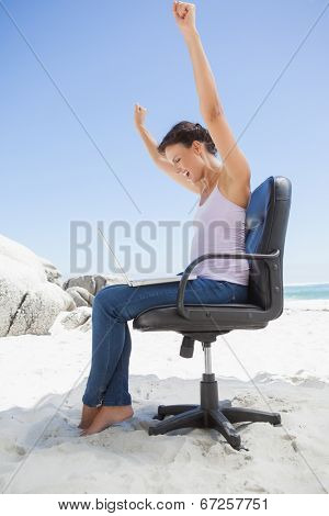 Cheering brunette using laptop on the beach sitting on swivel chair on a sunny day