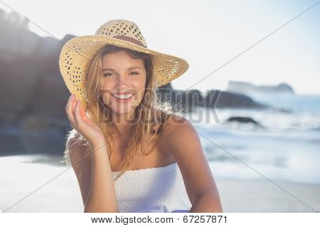 Beautiful smiling blonde in sundress sitting on the beach on a sunny day