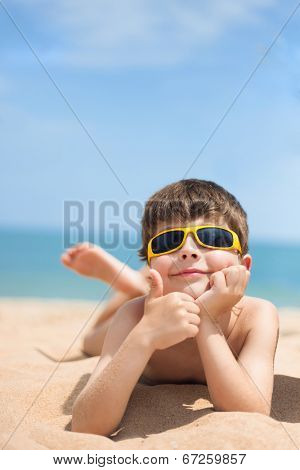 Image of little boy lying on the beach