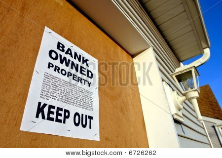 Real Estate Bank Owned Sign On House In Foreclosure