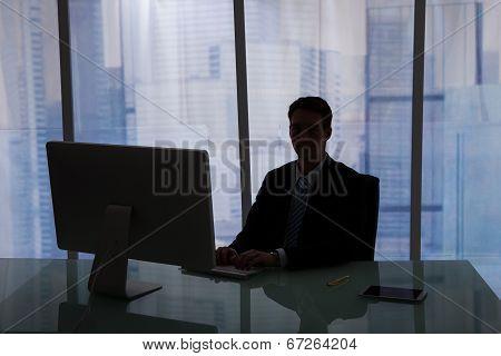 Businessman Working Overtime At Computer Desk