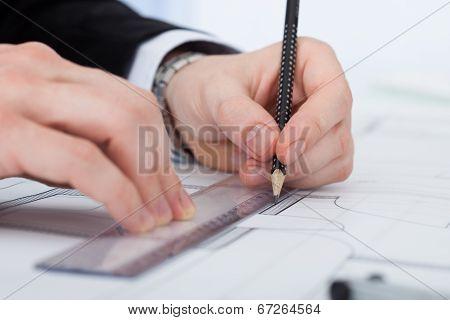 Businessman Working On Blueprint At Desk