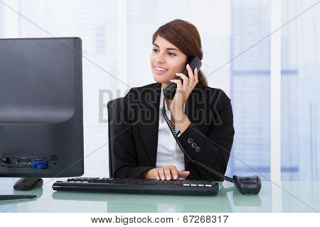 Businesswoman On Call While Using Computer At Desk