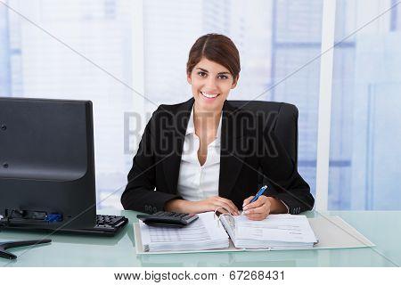 Confident Businesswoman Using Calculator At Office Desk