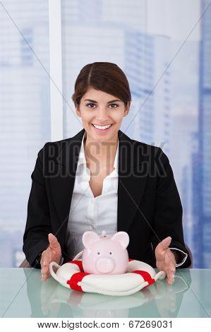 Confident Businesswoman Protecting Piggybank With Lifebuoy
