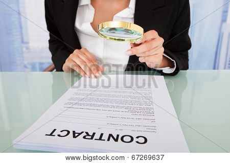Businesswoman Scrutinizing Contract With Magnifying Glass