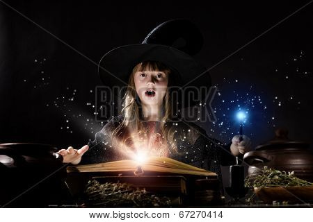 Little Halloween witch reading conjure from magic book