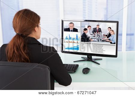 Businesswoman Video Conferencing With Team On Computer