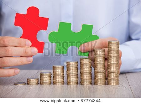 Businessman With Puzzle Pieces And Stacked Coins At Desk