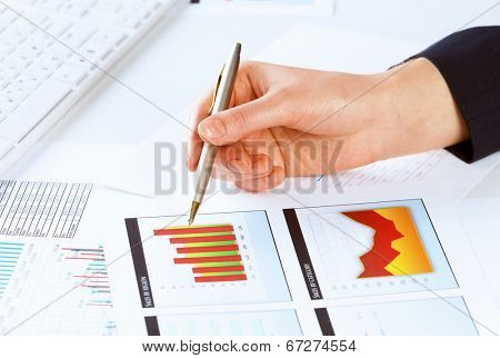 Close up of male hand holding pen and pointing at graphs