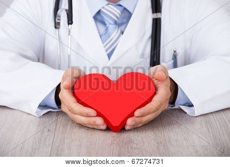 Midsection Of Doctor Holding Red Heart At Desk