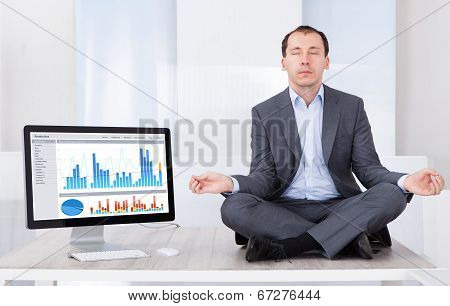 Businessman Mediating By Computer On Desk