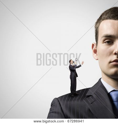 Miniature of businessman screaming in megaphone standing on boss shoulder