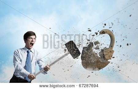 Young angry businessman crashing stone lock with hammer