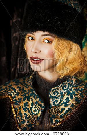 Portrait of a beautiful fashion model in a rich historical costume. Fur clothing. Vintage. Luxury style.