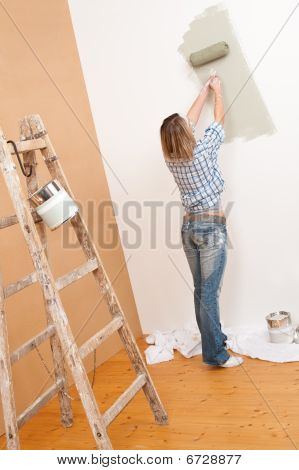 Home Improvement: Cheerful Woman With Paint Roller And Ladder