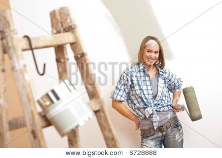 Home Improvement: Young Woman With Paint Roller And Ladder