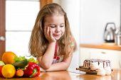 stock photo of brownie  - kid choosing between healthy vegetables and tasty sweets - JPG