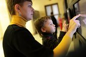image of realism  - Family using touch screen in a museum - JPG